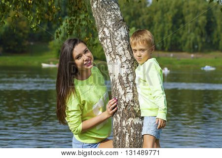 Young Mother and son playing in summer park. Concept of friendly family.