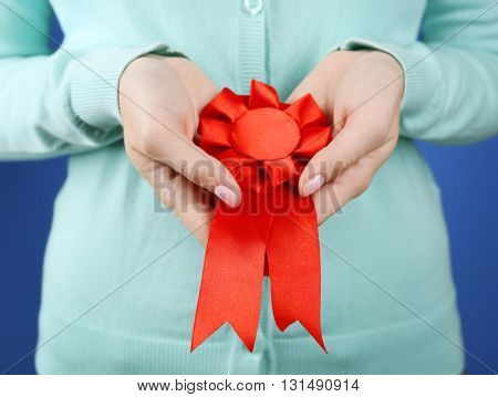 Woman with award ribbon. close-up