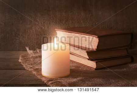 Books and candle on napkin on wooden table on wooden wall background