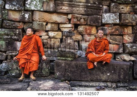 Siem Reap, Cambodia - December 28, 2013: Buddhist monks at the ancient temple of Bayon at Angkor, Siem Reap, Cambodia.