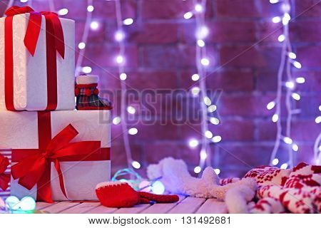 Christmas gift boxes and lights on the wooden table