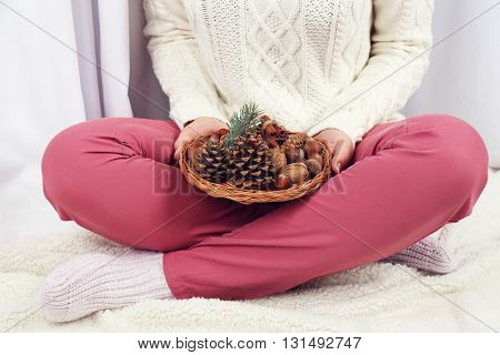 Wicker basket with Christmas decoration in woman hands, closeup