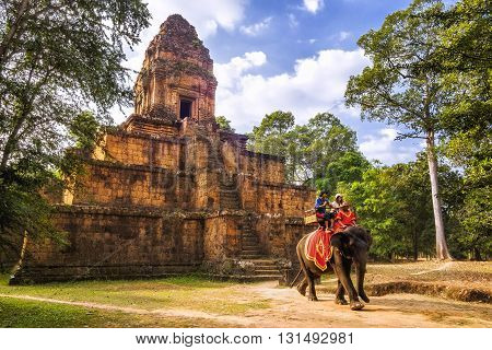 Siem Reap, Cambodia - December 29, 2013: Tourists riding elephant in front of ancient Khmer temple ruins at Angkor, Siem Reap, Cambodia.