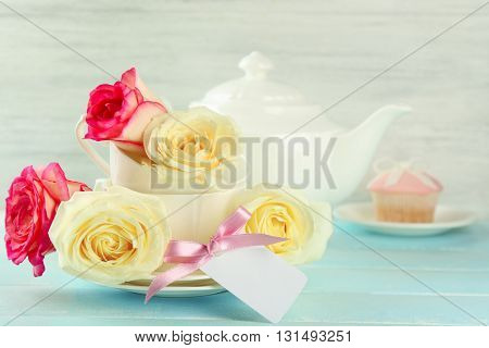 Happy Mother's day concept. Roses in a white cup with greeting card.
