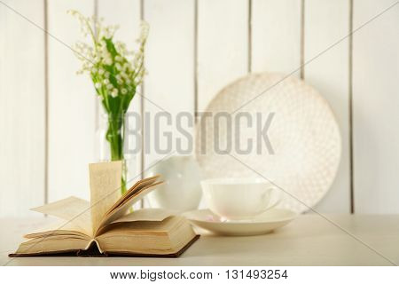 Open book with white tableware on table