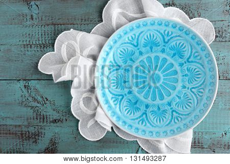 Empty plate and napkin on wooden background