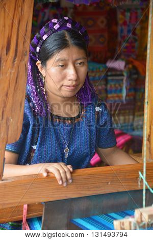 SANTA CATARINA PALOPO DE ATITLAN GUATEMALA NAY 01 2016: Portrait of a Mayan woman weaving a tissus. The Mayan people still make up a majority of the population in Guatemala.