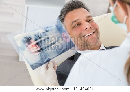 Dentist Holding Teeth X-ray In Front Of Happy Businessman In Clinic