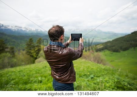 Adult european man taking selfie on tablet in mountains.