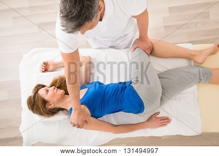 Masseur Doing Massage On Mature Woman In Spa