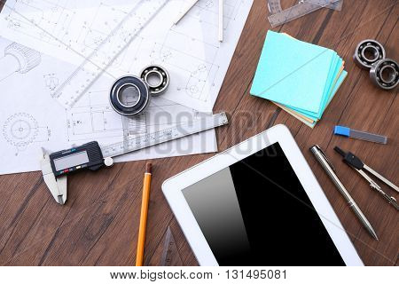 Tablet and engineering tools on wooden table, top view