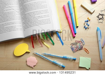 Open book with bookmarks on wooden table