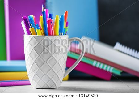 Stationery in cup on books background