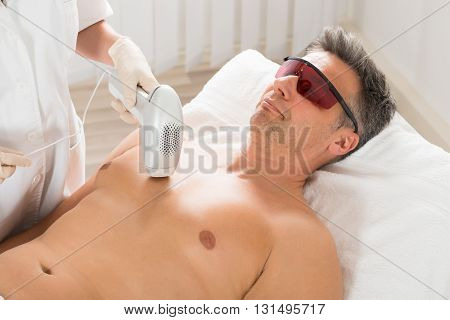 Beautician Giving Laser Epilation Treatment To Mature Man In Clinic