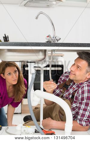 Woman Looking At Male Plumber Fixing Sink In Kitchen