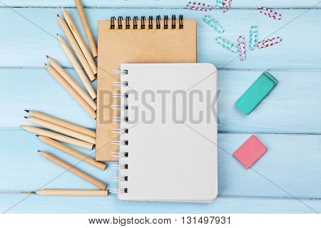 Office set with notebooks, colored pencils and erasers on blue background