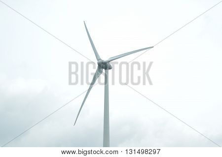 A wind power station photographed from below, against a cloudy sky.