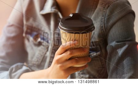Young woman in cafe holding coffee, closeup