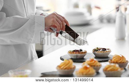 Female hands grating chocolate over fruit tarts.