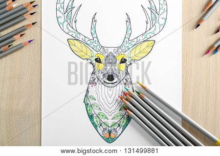 Adult anti stress coloring and crayons on wooden table, top view