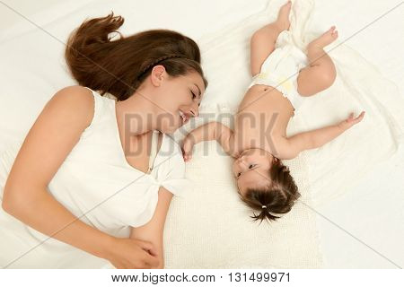 portrait of mother and baby lie on white