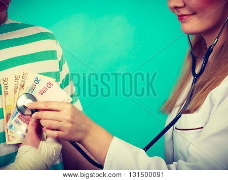 Corruption in medicine. Female doctor with stethoscope checking heart beating. Male bandaged hand with banknotes euro money.