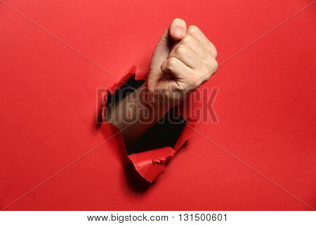 Male fist punching through red paper