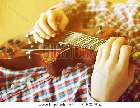 Young man playing electric guitar, close up