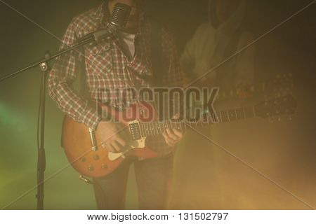 Young couple playing electric guitars on lighted foggy background