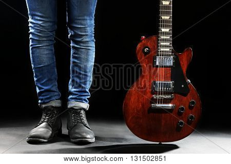 Young man in blue jeans standing with electric guitar on lighted dark background