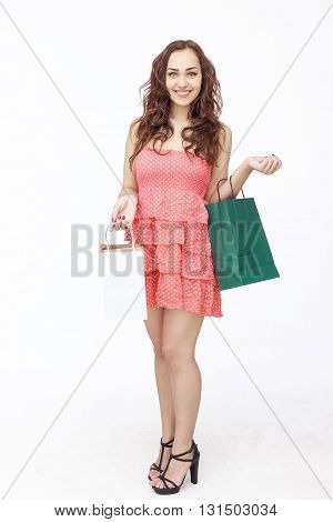 Happy young woman posing in pink dress with shopping bags isolated on white background