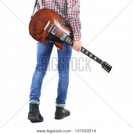 Young man in blue jeans standing back with electric guitar, isolated on white