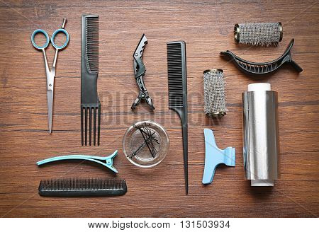 Hairdresser set with various accessories on wooden background