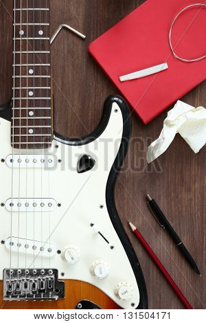 Guitar with notebook on wooden table closeup