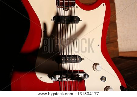 Electric guitar with shadow hand on wooden background