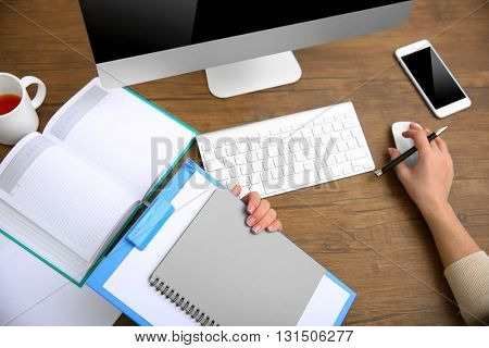 Work concept. Clipboard and notebook in woman hands. Computer and smart phone on wooden table