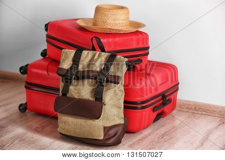 Suitcases and hat on white wall background