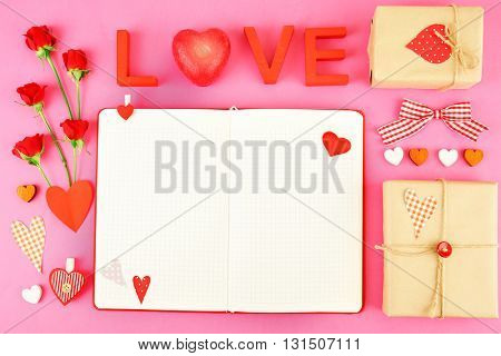 Notebook with gift and Valentine's decor on pink background, top view