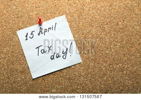 Tax day hand written reminder on April of 15th pinned to the board, top view