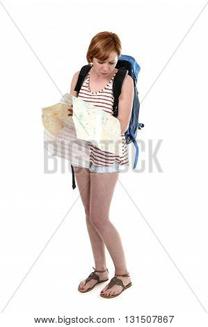 young attractive American tourist woman with red hair holding city map carrying backpacker rucksack and wearing shorts smiling happy isolated on white background in travel and vacation concept