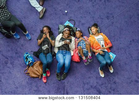 LONDON, UK - SEPTEMBER 19, 2016: People and families lying on the floor, resting and chatting. View from the top of stairs above the people