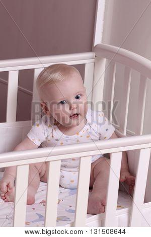 Little baby boy sitting in a crib