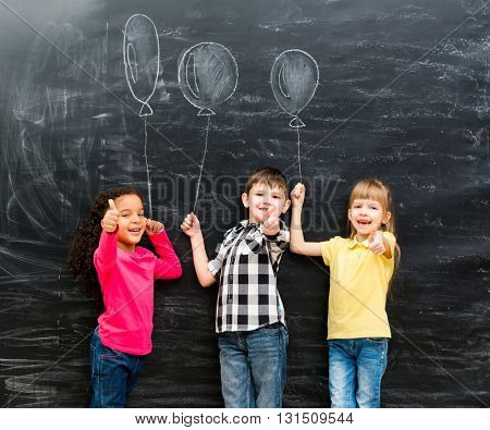 three smiling children with thumbs up keeping imaginaru drawn balloons on a chalky blackboard