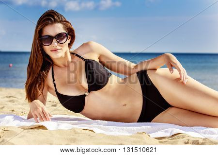 Beautiful Sexy Girl In Swimwear Laying On Sandy Beach. Sea Coast Visible In The Background.