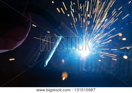 the welding spark light in close-up scenethe torch of welging machine with the spark light in blue