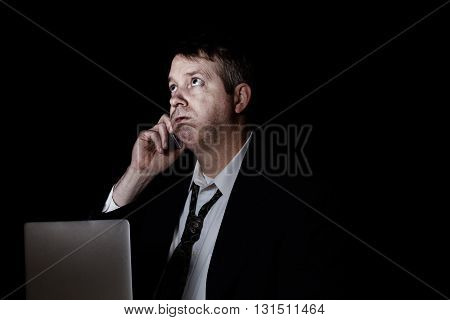 Side view of stressed business man on cell phone while working. Dark background with light on face.