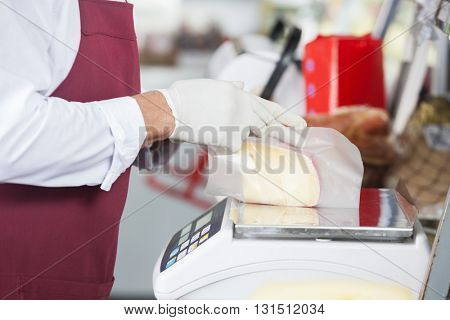 Salesman Wrapping Cheese On Weight Scale