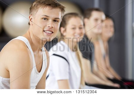 Man Smiling While Sitting With Friends In Gym