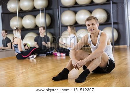 Confident Young Man Sitting On Floor At Gym
