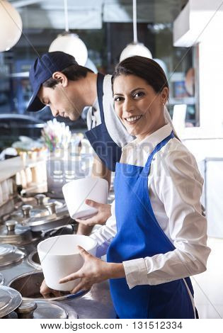 Female Worker Holding Cup In Ice Cream Parlor